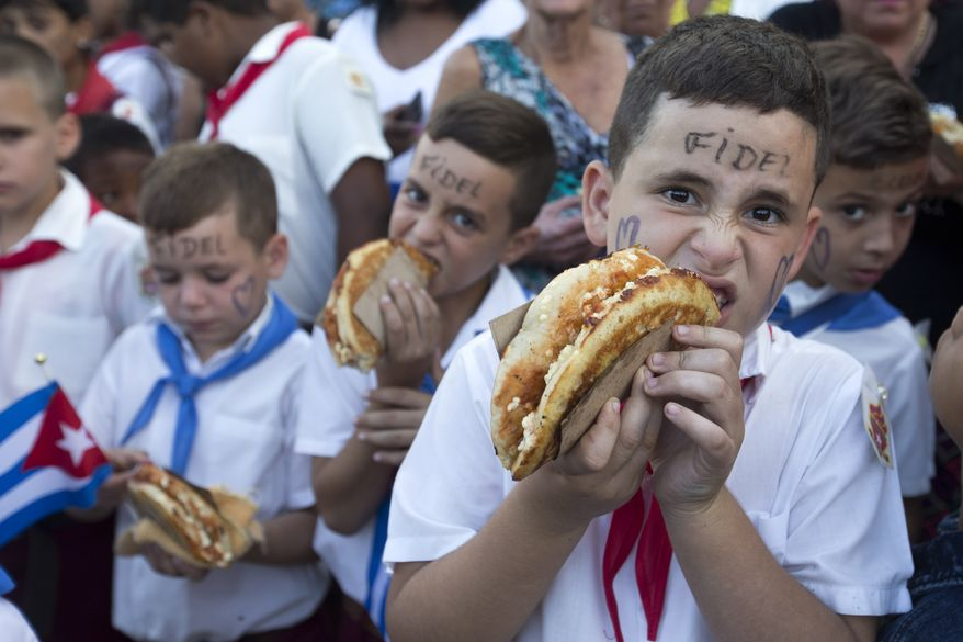School boys eat pizza as they line to see the ashes of Cuba's leader Fidel Castro being carried in a funeral procession on its way to the east of te country in Florida, Cuba, Thursday, Dec. 1, 2016. Castro's ashes are in a four-day journey across Cuba from Havana to their final resting place in the eastern city of Santiago. (AP Photo/Ricardo Mazalan)