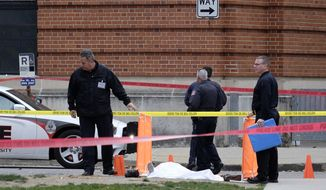 In this Monday, Nov. 28, 2016 file photo, police cover the body of a suspect outside Watts Hall on the campus of Ohio State University in Columbus, Ohio, following an attack on campus that left several people injured. The man, identified as Abdul Razak Ali Artan, plowed his car into a group of pedestrians and began stabbing people with a butcher knife Monday before he was shot to death by a police officer. Leaders of the mosque say they don't remember Artan, and Ohio State's Muslim and Somali student groups say he wasn't affiliated with their organizations. (Adam Cairns/The Columbus Dispatch via AP, File)