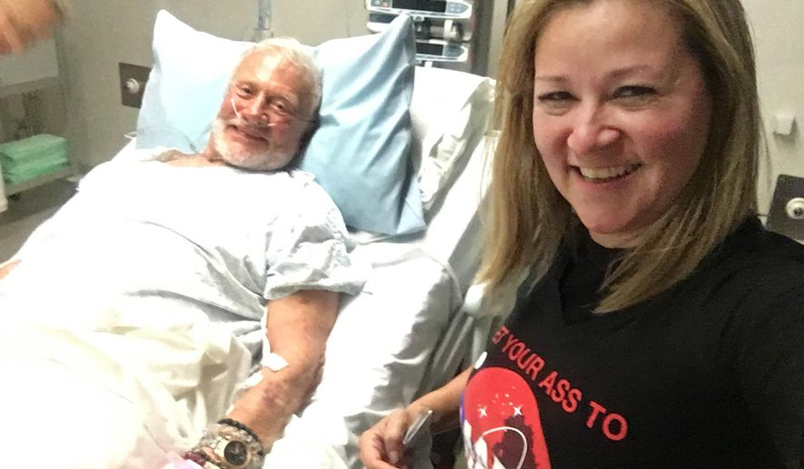 In this Thursday, Dec. 1, 2016 photo provided by Christina Korp, right, Buzz Aldrin lies in a hospital bed in Christchurch, New Zealand. Aldrin, the second man to walk on the moon, was evacuated from the South Pole to New Zealand where he was hospitalized in stable condition. (Christina Korp via AP)