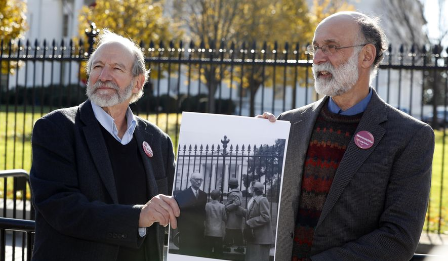 CORRECTS THAT THEY ARE SEEKING AN EXONERATION NOT A PARDON - Michael, left, and Robert Meeropol, the sons of Ethel Rosenberg, pose similar to an old photograph of them, before they attempt to deliver a letter to President Barack Obama in an effort to obtain a exoneration for their mother Ethel Rosenberg, in front of the White House, Thursday, Dec. 1, 2016 in Washington. Ethel Rosenberg was executed, along with her husband, Julius, in 1953 after being convicted in a Cold War atomic spying case that captivated the country. (AP Photo/Alex Brandon)
