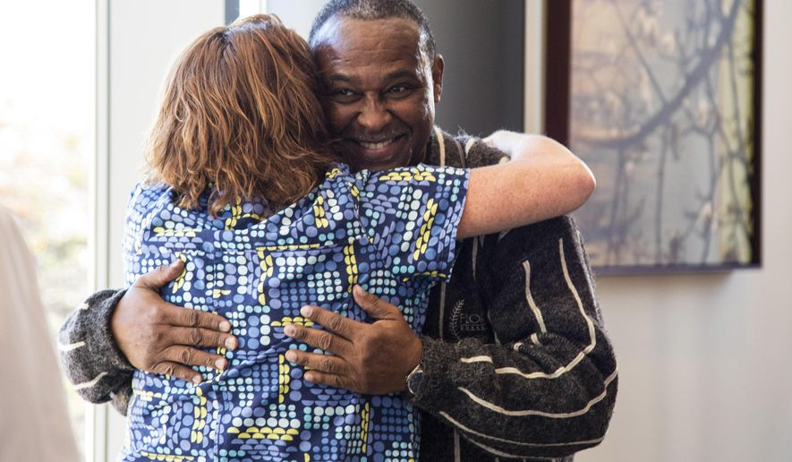 ADVANCE FOR USE SATURDAY, DEC. 3, 2016 AND THEREAFTER - In this Nov. 9, 2016 photo, Anthony Johnson, hugs nurse Cindy Chiodini of OSF Saint  Anthony Medical Center in Rockford, Ill. Johnson was receiving a check for $3,600 from the Rockford Fire Department Local 413 that raised funds for cancer patients. Johnson has undergone radiation and chemotherapy after his cancer diagnosis in August. He has been unable to find employment because of his condition but hopes to get back to work following his final treatments in January. (Kayli Plotner/Rockford Register Star via AP)