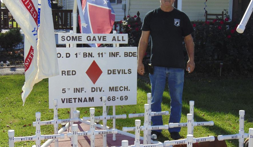"""ADVANCE FOR USE SUNDAY, DEC. 4, 2016 AND THEREAFTER - In this Nov. 4,  2016 photo, Vietnam veteran Donald Dorn stands with the memorial he built in his front yard in Dieterich, Ill., to honor the 22 young soldiers in his company who were killed in action. """"I'll keep it up as long as I can continue to maintain it,"""" said Dorn. (Dawn Schabbing/Effingham Daily News via AP)"""