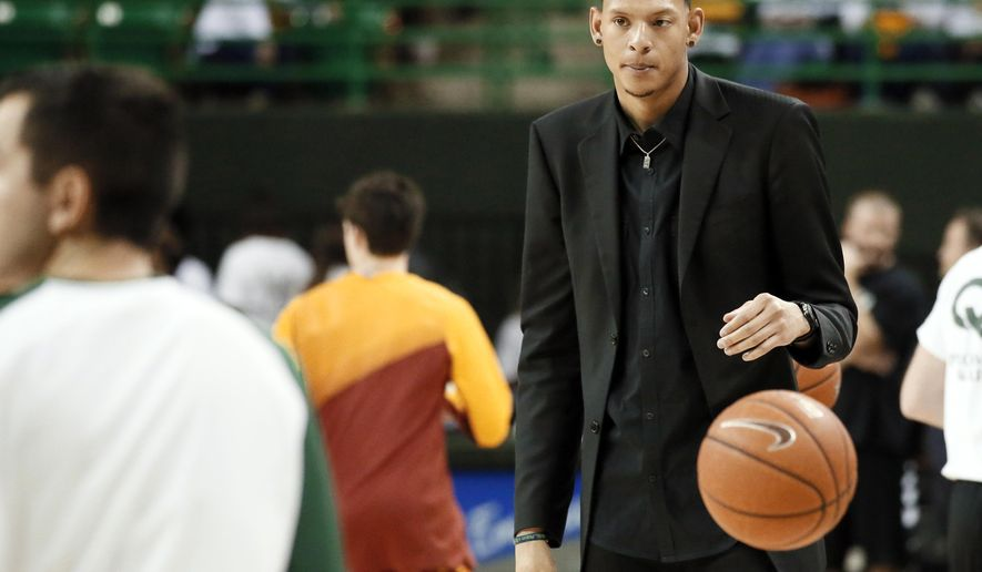 FILE - In this Jan. 14, 2015, file photo, Baylor student assistant Isaiah Austin prepares to toss a ball in as players run through drills before an NCAA college basketball game against Iowa State in Waco, Texas. Former Baylor standout Isaiah Austin has been cleared to play basketball again, 2 1/2 years after he was diagnosed with Marfan syndrome during a physical before the NBA draft. Austin revealed on his Instagram account this week that his doctor has given him the go-ahead to again pursue his dream of playing professional basketball.  (AP Photo/Tony Gutierrez, File)