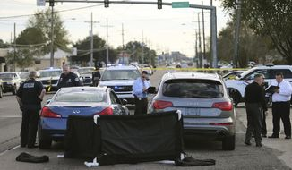 The body of former NFL player Joe McKnight lies between the shooter's vehicle at left and his Audi SUV at right as the Jefferson Parish Sheriff's Office investigates the scene in Terrytown, La., on Thursday, Dec. 1, 2016. (Michael DeMocker  /NOLA.com The Times-Picayune via AP)