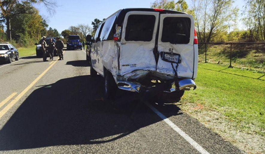 In this image taken from video, a wrecked school van sits on the road as investigators survey the scene in Trinity, Texas, Thursday, Dec. 1, 2016. A young girl died after the school van, that had stopped to pick up children, was rear-ended by a truck on the rural East Texas highway with multiple students and the van driver also injured.  (KTRE via AP)