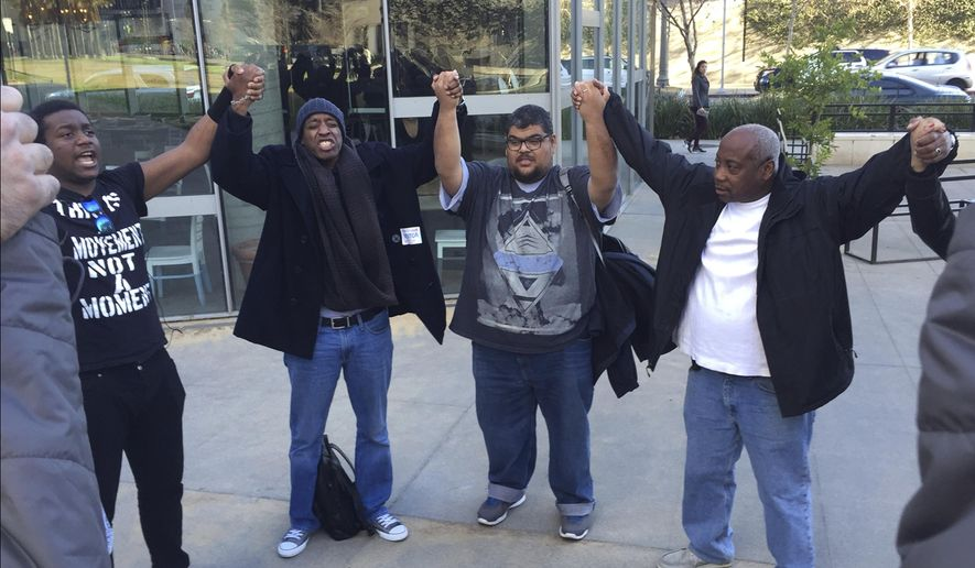 "FILE- In this Feb. 2, 2016 file photo, activists hold hands and pray outside outside Los Angeles Police Department headquarters following the police commission's decision finding that the shooting of Charly ""Africa"" Keunang was justified in Los Angeles. Three Los Angeles police officers who fatally shot Keunang, a black homeless man on Skid Row last year, will not face criminal charges according to a report released Thursday, Dec. 1, by the district attorney. (AP Photo/Amanda Lee Myers, File)"