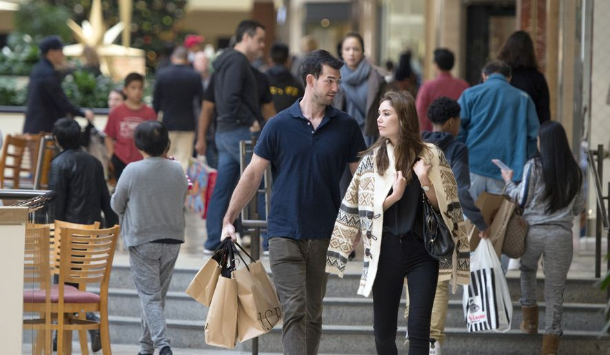 In this Friday, Nov. 25, 2016, file photo, Eric Denker and his wife, Jalen Denker, of Irvine, take advantage of sales to buy suits for business school interviews at South Coast Plaza in Costa Mesa, Calif. On Friday, Dec. 2, 2016, the U.S. government issues the November jobs report. (Jeff Gritchen/The Orange County Register via AP, File)