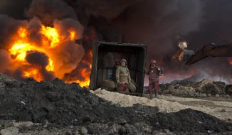 Firefighters work to quell an oil fire set by Islamic State militants in Qayara, south of Mosul, Iraq, on Monday, Nov. 28, 2016. (AP Photo/Maya Alleruzzo)