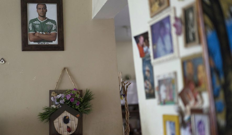 A framed picture of Brazil's Chapecoense soccer player Neto, who survived the plane crash in Colombia that killed most of his teammates, hangs inside his parent's home in Rio de Janeiro, Brazil, Thursday, Dec. 1, 2016. Neto's wife told his family that Neto told her the day of the flight that he had had a dream that his airline crashed. (AP Photo/Leo Correa)