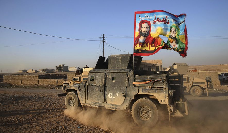 "An Iraqi Special Forces vehicle displays a Shiite flag bearing the likeness of Imam Hussein and Imam Ali with Arabic words reading ""At your service Hussein"" in Mosul, Iraq. State-sanctioned Shiite militias are positioning themselves to control areas liberated from Islamic State militants in northern Iraq, opening the door to fresh domestic and regional conflict and raising concerns among religious and ethnic minorities. (Associated Press/File)"