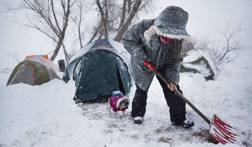 "In this Tuesday, Nov. 29, 2016 photo, Loretta Reddog, of Placerville, Calif., shovels a walkway to her tent while followed by her dog Gurdee Bean at the Oceti Sakowin camp where people have gathered to protest the Dakota Access oil pipeline in Cannon Ball, N.D. ""I'm scared. I'm a California girl, you know?"" said Reddog who arrived several months ago with her two dogs and has yet to adjust to the harsher climate. Reddog has confidence in the camp community. ""Everybody's really stepping up and taking care of each other,"" she said. (AP Photo/David Goldman)"