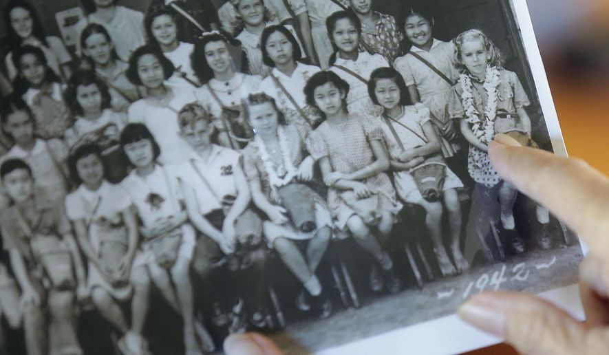 Joan Rodby points to herself in a 1942 photo, in Makawao, Hawaii on Friday, Nov. 18, 2016. After the Pearl Harbor attack, schools required students to carry gas masks with them at all times - even when posing for their class photo. (AP Photo/Rick Bowmer)