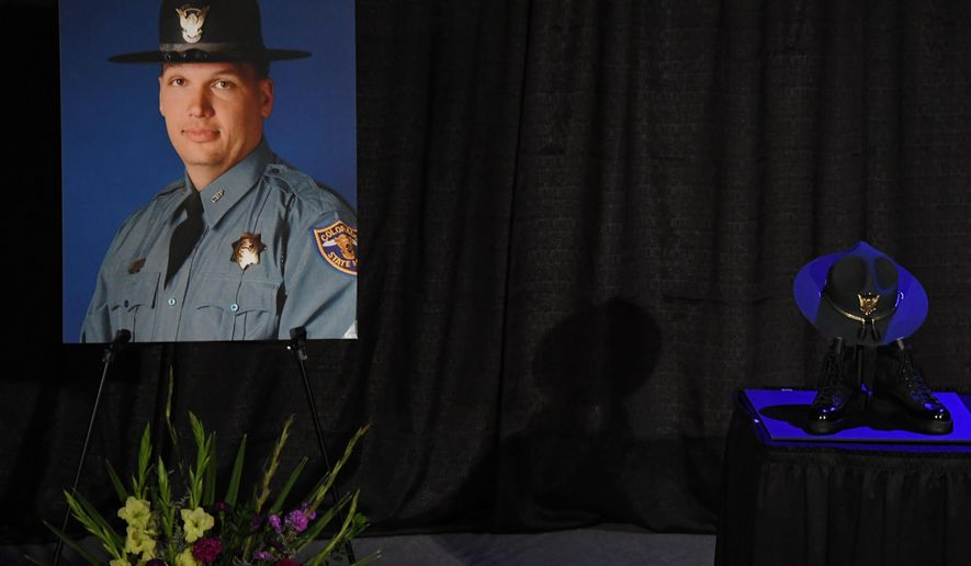 A portrait of fallen Colorado State Patrol Trooper Cody Donahue, who was killed during an accident investigation, is displayed next to his hat and boots during a service at Denver First Church of Nazarene, Friday, Dec. 2, 2016, in Englewood, Colo. (RJ Sangosti  /The Denver Post via AP)
