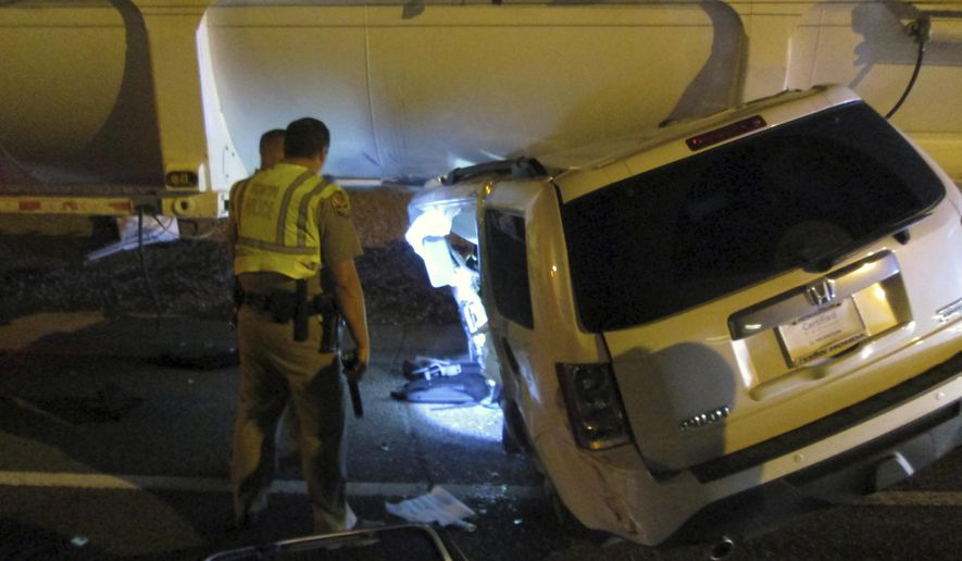 This photo provided by the Arizona Department of Public Safety shows an SUV wedged under a tractor-trailer on the westbound Loop 202 freeway in Chandler, Ariz. on Friday, Dec. 2, 2016. Authorities say a woman survived a three-vehicle accident in which her SUV was involved in two collisions that resulted in her vehicle being wedged until a tractor-trailer. The SUV's top was partially sheared off and firefighters had to extricate the woman.(Arizona Department of Public Safety via AP)