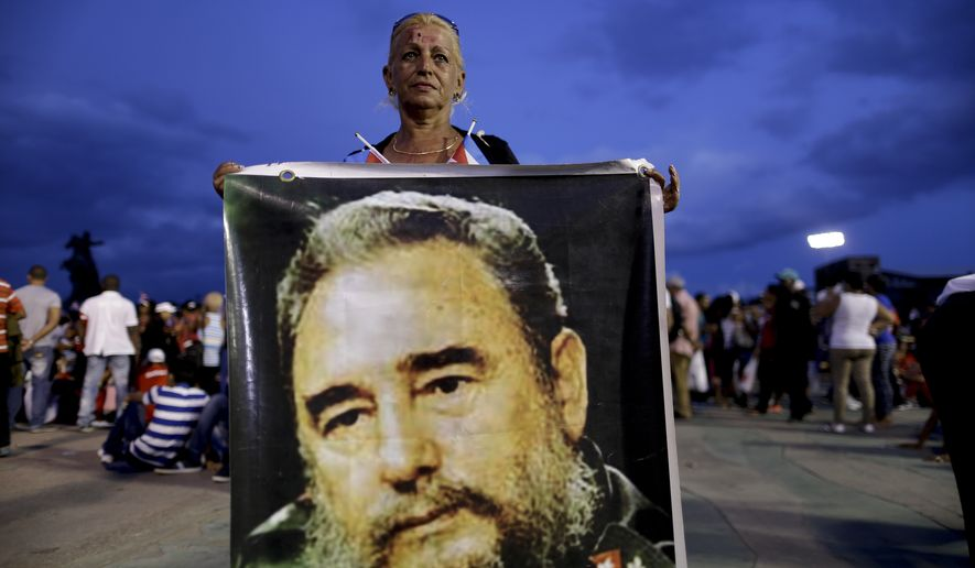 A woman holds a picture of Fidel Castro before a rally honoring Cuba's leader before his burial Sunday at the Plaza Antonio Maceo in Santiago, Cuba, Saturday, Dec. 3, 2016. After a a four-day journey across the island, retracing the path of his triumphant march into Havana nearly six decades ago a small, Cuban-flag covered cedar coffin containing the remains of the 90-year-old leader arrived in Santiago to be buried Sunday. (AP Photo/Natacha Pisarenko)