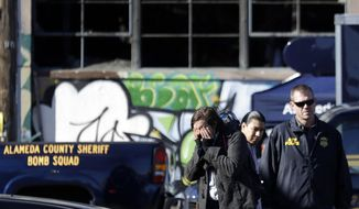 A unidentified man covers his face outside of a warehouse that was destroyed by a fire Saturday, Dec. 3, 2016, in Oakland, Calif.   Oakland fire chief Teresa Deloche-Reed said many people were unaccounted for as of Saturday morning and authorities were working to verify who was in the cluttered warehouse when the fire broke out around 11:30 p.m. Friday.  (AP Photo/Marcio Jose Sanchez)