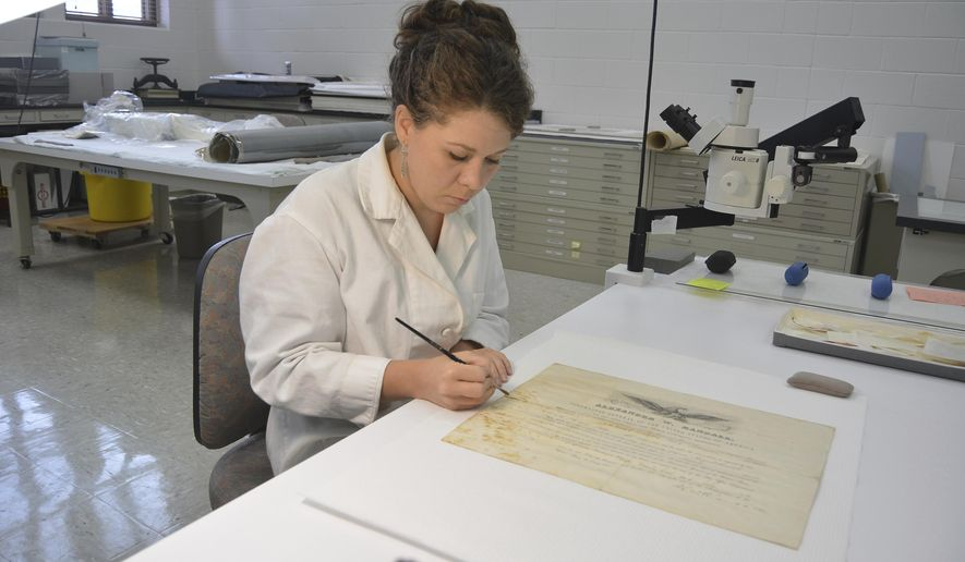 In this June 14, 2016 photo, Hilary Lefevere brushes away mold on a historical document at the Ford Conservation Center, in Omaha, Neb. The document appointed August Raasch the postmaster of Norfolk in 1868. (Dennis Meyer/The Norfolk Daily News via AP)