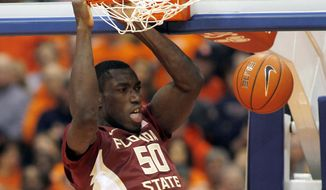 FILE - In this Jan. 11, 2015, file photo, Florida State's Michael Ojo jams in the second half of an NCAA college basketball game against Syracuse in Syracuse, N.Y. After sitting out last year due to a knee injury, Florida State center Michael Ojo already has two double-figure scoring games and has markedly improved at the free throw line.  (AP Photo/Nick Lisi, File)