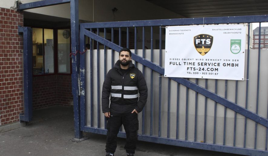 In this Oct. 19, 2016 photo Naji Negmah, a 24-year old asylum seeker from Damascus, stands in front of an asylum seeker home in Berlin where he works as a guard. A start-up company in Berlin is trying to play a role in helping integrate last year's flood of migrants into the German workforce with a tailor-made online job market for new arrivals. (AP Photo/Jona Kallgren)