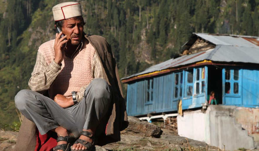 "In this Tuesday Oct. 4, 2016 photo, Jabe Ram speaks on a mobile phone outside his home on the upper end of Malana village in the northern Indian state of Himachal Pradesh. Malana has become one of the world's top stoner destinations, and a symbolical battleground for India's fight against 'charas,' the black and sticky hashish that has made the village famous. ""They want us to completely stop growing marijuana. But we keep sowing it,"" Ram said. ""If the government helped us in some way and protected us from hunger and cold, we would maybe consider stopping. Obviously, we are not going to go hungry. Even if we have to go to jail for it, so be it."" (AP Photo/Rishabh R. Jain)"