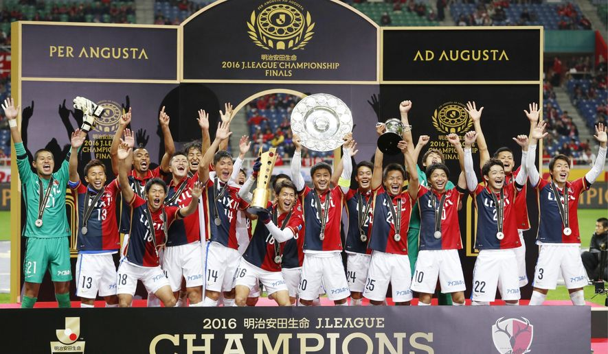 Kashima Antlers players celebrate with trophies after beating Urawa Reds 2-1 in their second leg soccer match of the J-League Championship Final at Saitama Stadium in Saitama, near Tokyo, Saturday, Dec. 3, 2016. Kashima claimed their eighth title. (Yohei Kanasashi/Kyodo News via AP)