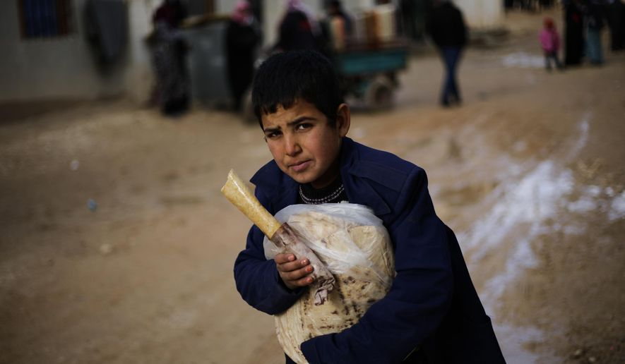 A Syrian boy displaced with his family from eastern Aleppo holds a sandwich and bread bag in the village of Jibreen south of Aleppo, Syria, Saturday, Dec. 3, 2016. Aid agencies say that more than 30,000 people have fled rebel-held eastern neighborhoods of Aleppo that have been under tight siege since July. Over the past two weeks, government forces launched an offensive in which they regained control of nearly half areas that had been held by insurgents in their deepest push since the city became contested in July 2012.(AP Photo/Hassan Ammar)