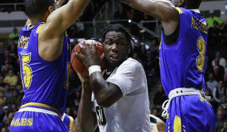 Purdue forward Caleb Swanigan controls the basketball in between Morehead State guard Miguel Dicent, left, and Morehead State forward Keion Alexander, right, in the first half of an NCAA college basketball game, Saturday, Dec. 3, 2016, in West Lafayette, Ind. (AP Photo/R Brent Smith)