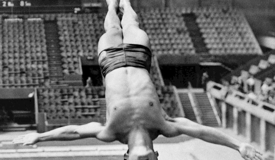 FILE - Int his July 27, 1948, file photo, Sammy Lee, member of the U.S. Olympic diving team, dives from the top of the diving tower during training at the London Olumpics at the Empire Pool in Wembley, England. Lee, a two-time Olympic gold medal-winning diver who later mentored four-time Olympic diving champion Greg Louganis, died Friday, Dec. 2, 2016, of pneumonia in Newport Beach, Calif., the University of Southern California said Saturday, Dec. 3. He was 96. (AP Photo/Laurence Harris, File)
