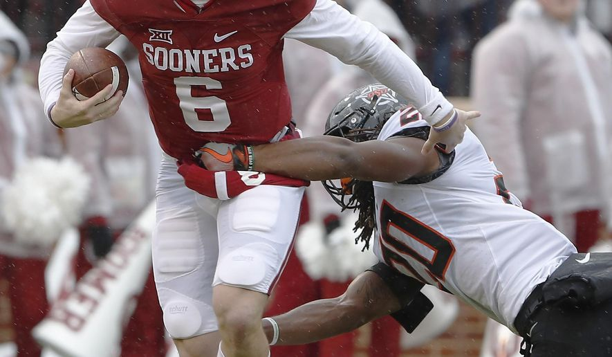 Oklahoma quarterback Baker Mayfield (6) is sacked by Oklahoma State linebacker Jordan Burton (20) during the first half of an NCAA college football game, Saturday, Dec. 3, 2016, in Norman, Okla. (AP Photo/Alonzo Adams)