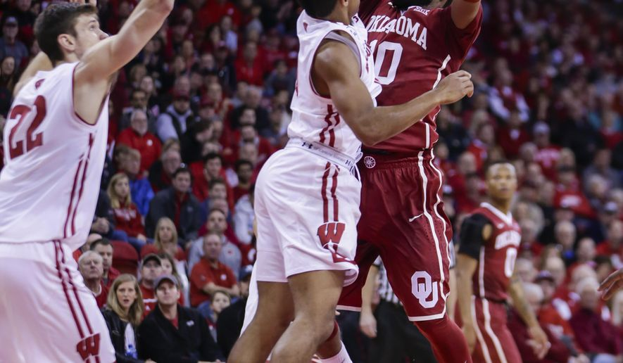 Oklahoma's Jordan Woodard (10) shoots against Wisconsin's D'Mitrik Trice (0) and Ethan Happ (22) during the first half of an NCAA college basketball game Saturday, Dec. 3, 2016, in Madison, Wis. (AP Photo/Andy Manis)