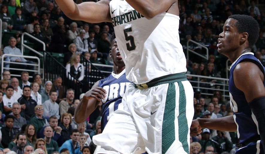 Michigan State's Cassius Winston (5) puts up a driving layup and draws a foul against Oral Roberts' Aaron Young, right, during the first half of an NCAA college basketball game, Saturday, Dec. 3, 2016, in East Lansing, Mich. (AP Photo/Al Goldis)