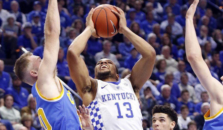 Kentucky's Isaiah Briscoe (13) shoots while defended by, from left, UCLA's Bryce Alford, Lonzo Ball, and Thomas Welsh during the first half of an NCAA college basketball game, Saturday, Dec. 3, 2016, in Lexington, Ky. (AP Photo/James Crisp)