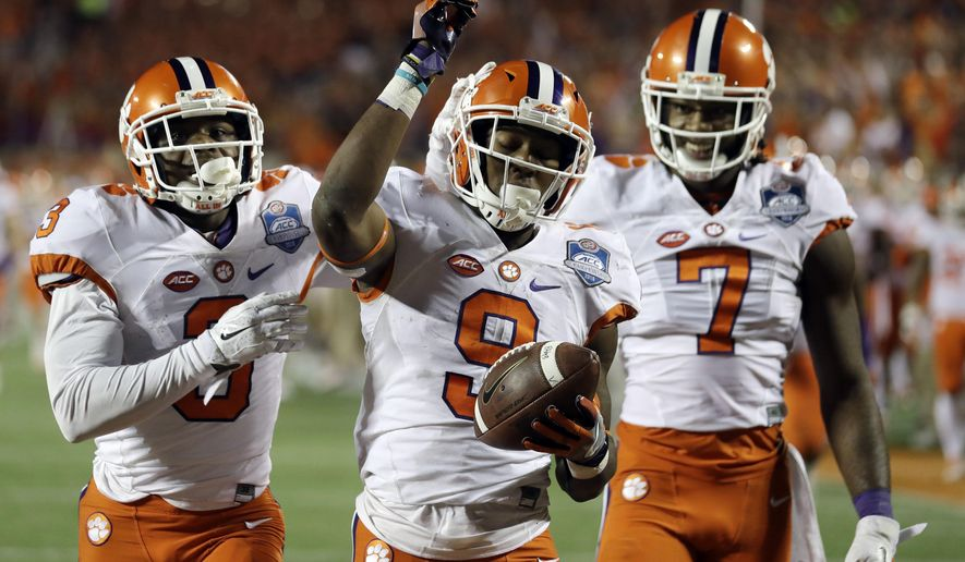 Clemson wide receivers Artavis Scott (3) and Mike Williams (7), congratulate running back Wayne Gallman (9) after Gallman scored a touchdown during the second half of the Atlantic Coast Conference championship NCAA college football game against Virginia Tech , Saturday, Dec. 3, 2016, in Orlando, Fla. (AP Photo/Chris O'Meara)