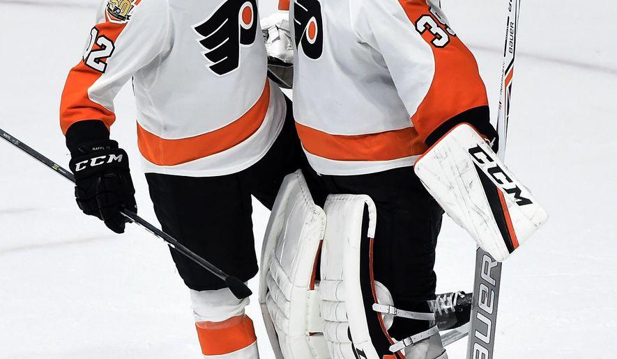 Philadelphia Flyers left wing Michael Raffl (12), of Austria, congratulates goalie Steve Mason (35) following the team's win against the Nashville Predators in an NHL hockey game Sunday, Dec. 4, 2016, in Nashville, Tenn. The Flyers won 4-2. (AP Photo/Mark Zaleski)