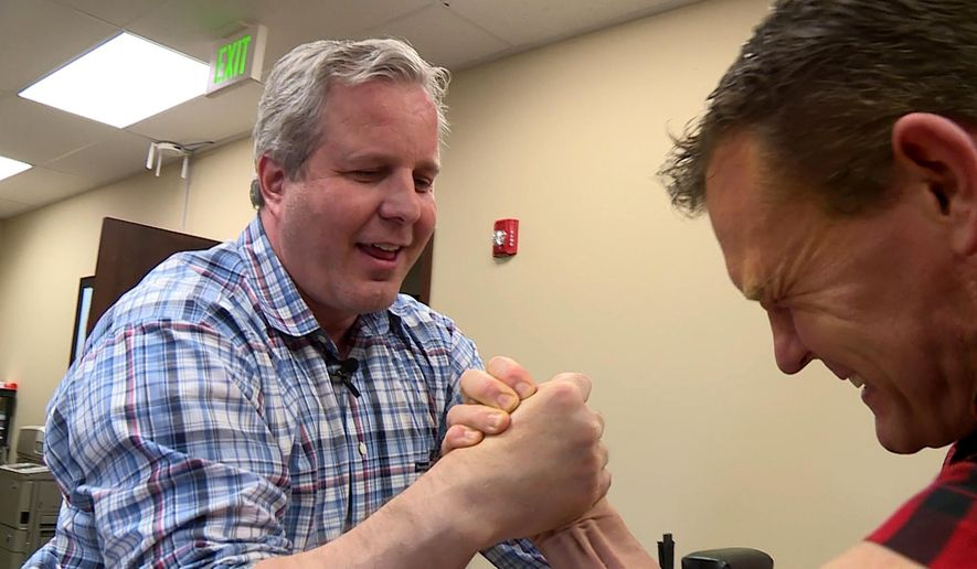 In this image taken from video on Nov. 15, 2016, Robert Baxter arm-wrestles Spencer Lightningfire in his South Jordan, Utah, office. Baxter is up to his neck in competition in both the restaurant business and the world of arm wrestling, but says facing off against an enemy has brought him some of the best friends he'll ever have.  (Ray Boone/KSL-TV/The Deseret News via AP)