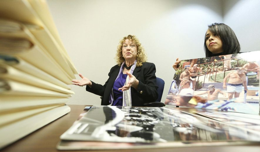 In this Nov. 22, 2016, photo, Lynn Goya, Clark County Clerk, left, and senior office specialist Rocio Leon show of some of the records that are being digitized at the Clark County Government Center in Las Vegas. Everything from government documents from the 1800s to photos from investigations are being indexed so they can be easily searchable. (Brett Le Blanc/Las Vegas Review-Journal via AP)