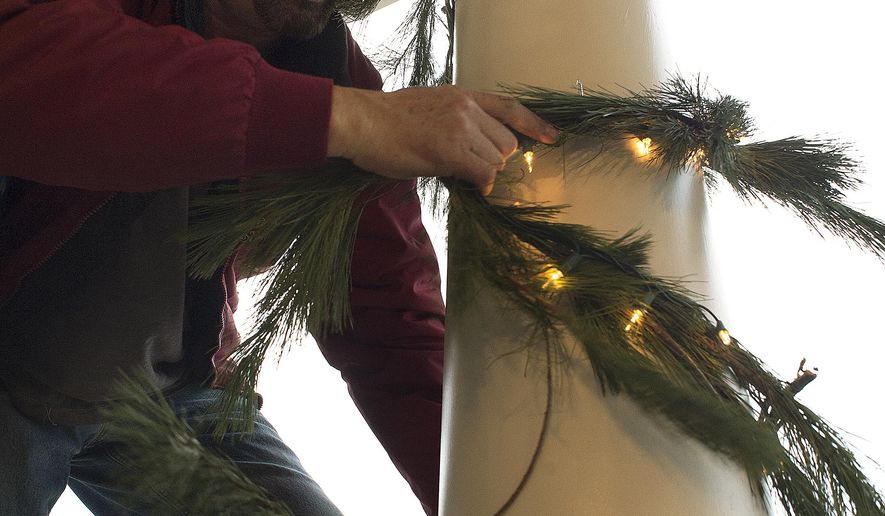 ADVANCE FOR WEEKEND EDITIONS, DEC. 3-4 - In this Nov. 23, 2016 photo, Ron Layman, owner of The King of Christmas, wraps garland and lights on the column of a house in Frederick, Md. (Dan Gross/The Frederick News-Post via AP)