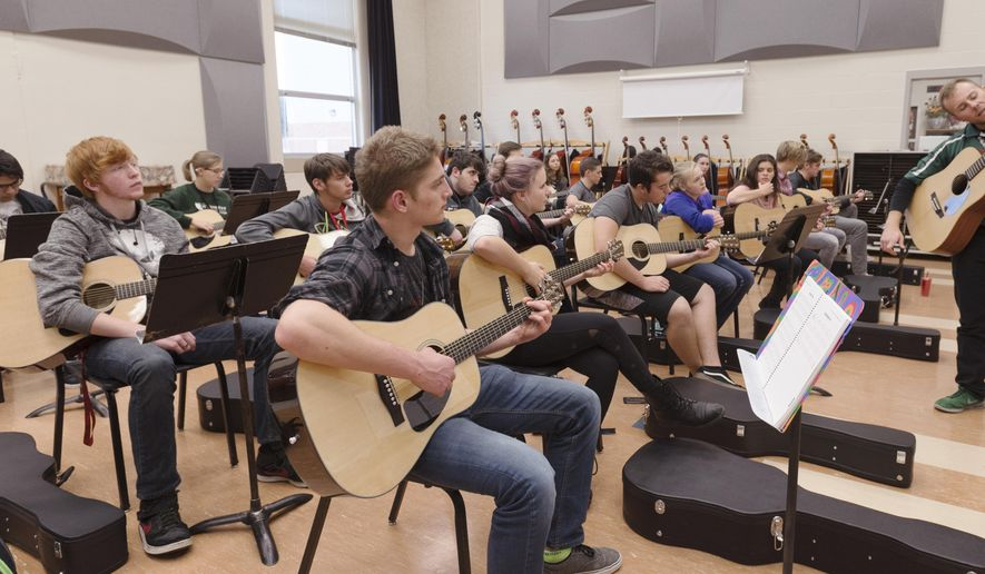 In this Tuesday, Nov. 22, 2016 photo, music teacher Jason Lenz shows his guitar class how to finger a chord at Lincoln Southwest High School in Lincoln, Neb. (Ted Kirk  /The Journal-Star via AP)