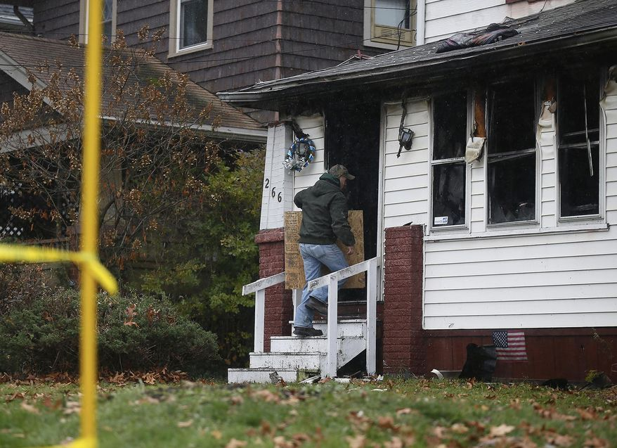 Kyle Otto of J. Bowers Construction boards up a burned home in Akron, Ohio, on Saturday, Dec. 3, 2016 after a deadly fire. (Leah Klafczynski/Akron Beacon Journal via AP)