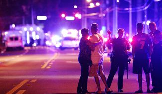 2016 AP YEAR END PHOTOS - Orlando Police officers direct family members away from a fatal shooting at Pulse nightclub in Orlando, Fla., on June 12, 2016. Omar Mateen, a 29-year-old security guard, killed 49 people and wounded 53 others in the mass shooting. (AP Photo/Phelan M. Ebenhack, File)