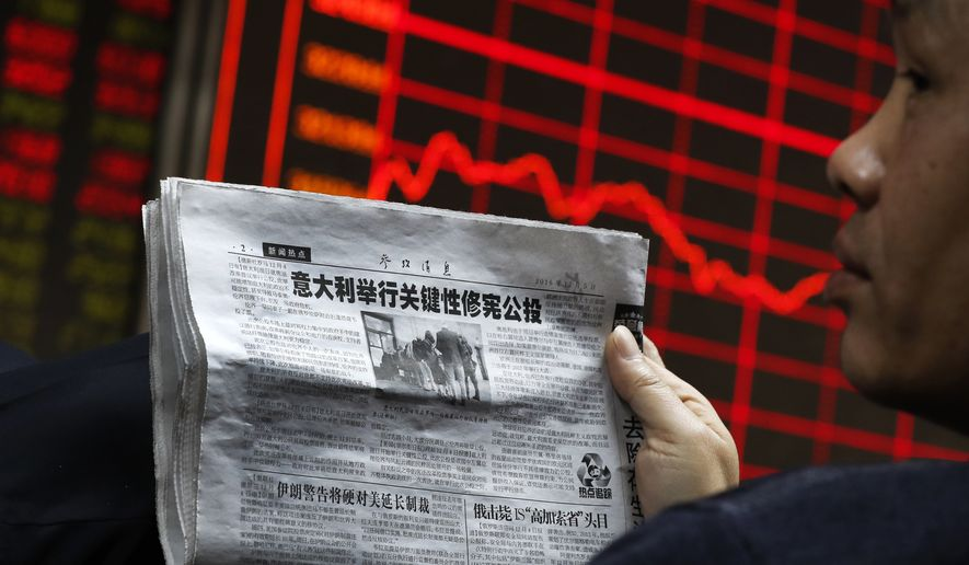 A man holds a newspaper reporting a story of constitutional change in Italy as he looks at an electronic board displaying stock prices at a brokerage house in Beijing, Monday, Dec. 5, 2016. Asian shares tumbled Monday after Italian voters' rejected constitutional changes, raising questions over whether Italy will stay in the European Union and keep using the euro. (AP Photo/Andy Wong)