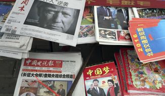 """FILE - In this Nov. 10, 2016 file photo, a front page of a Chinese newspaper with a photo of U.S. President-elect Donald Trump and the headline """"Outsider counter attack"""" is displayed at a newsstand in Beijing, China. With Trump's latest tweets touching on sensitive issues, China must decide how to handle an incoming American president who relishes confrontation and whose online statements appear to foreshadow shifts in foreign policy. China awoke Monday, Dec. 5, to criticism from Trump on Twitter, days after it responded to his telephone conversation with Taiwan's president by accusing the Taiwanese of playing a """"little trick"""" on Trump. (AP Photo/Ng Han Guan)"""