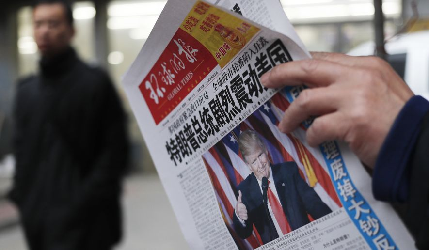 "In this Nov. 10, 2016, file photo, a man reads a newspaper with the headline that reads ""U.S. President-elect Donald Trump delivers a mighty shock to America"" at a newsstand in Beijing. With Trump's latest tweets touching on sensitive issues, China must decide how to handle an incoming American president who relishes confrontation and whose online statements appear to foreshadow shifts in foreign policy. (AP Photo/Andy Wong, File)"