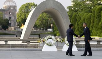 In this May 27, 2016, file photo, U.S. President Obama, right, shakes hands with Japanese Prime Minister Shinzo Abe at Hiroshima Peace Memorial Park in Hiroshima, western Japan, as Obama became the first sitting U.S. president to visit the site of the world's first atomic bomb attack. Abe said Monday, Dec. 5, he will visit Pearl Harbor with Obama at the end of this month, becoming the first leader of his country to go to the U.S. Naval base in Hawaii that Japan attacked in 1941, propelling the United States into World War II. Atomic Bomb Dome is seen in the background. (AP Photo/Carolyn Kaster, File)