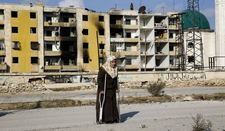 In this Sunday, Dec. 4, 2016, photo, Nisrin Malaji returns to her looted home in the Hanano district of eastern Aleppo, Syria. It's a painful homecoming shared by hundreds of Syrians who are returning to areas devastated by years of war and then retaken from the city's embattled rebels in a recent government offensive. (AP Photo/Hassan Ammar)