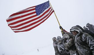 Military veterans huddle together to hold an American flag against strong winds during a march to a closed bridge outside the Oceti Sakowin camp where people have gathered to protest the Dakota Access oil pipeline in Cannon Ball, N.D., Monday, Dec. 5, 2016. (AP Photo/David Goldman)