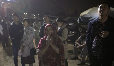 People stand outside a hotel on fire in Karachi, Pakistan, Monday, Dec. 5, 2016. A massive fire swept through a four-star hotel in the southern port city of Karachi on Monday, officials said. (AP Photo/Shakil Adil)