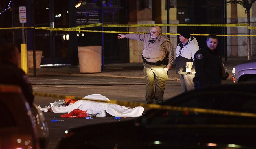 In this Dec. 4, 2016 photo, the body of a male suspect lies in a parking lot of the in American Fork, Utah, where he was shot and killed by police following a brief pursuit. Sheriff's Sgt. Spencer Cannon said the man refused orders to drop his gun and officers wound up firing shots. (Francisco Kjolseth/The Salt Lake Tribune via AP)