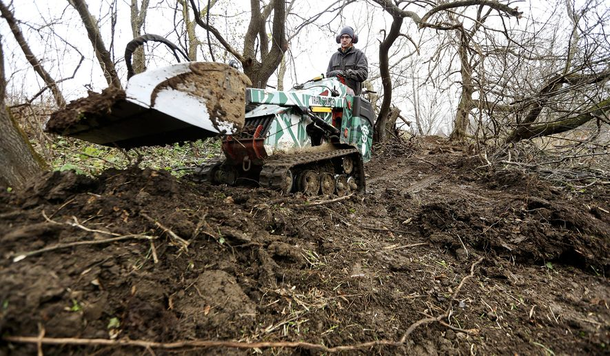 In this Dec. 1, 2016 photo, Warren Bartholomew, with Trail Source in Rosemount, Minn., works on the Cloie Creek Park Mountain Bike Trail in Asbury, Iowa. The mountain bike group, Tri-State Mountain Bike Riders, is leading the effort to build more than two miles of dirt trails through wooded land in the eastern Iowa city of Asbury. (Nicki Kohl/Telegraph Herald via AP)