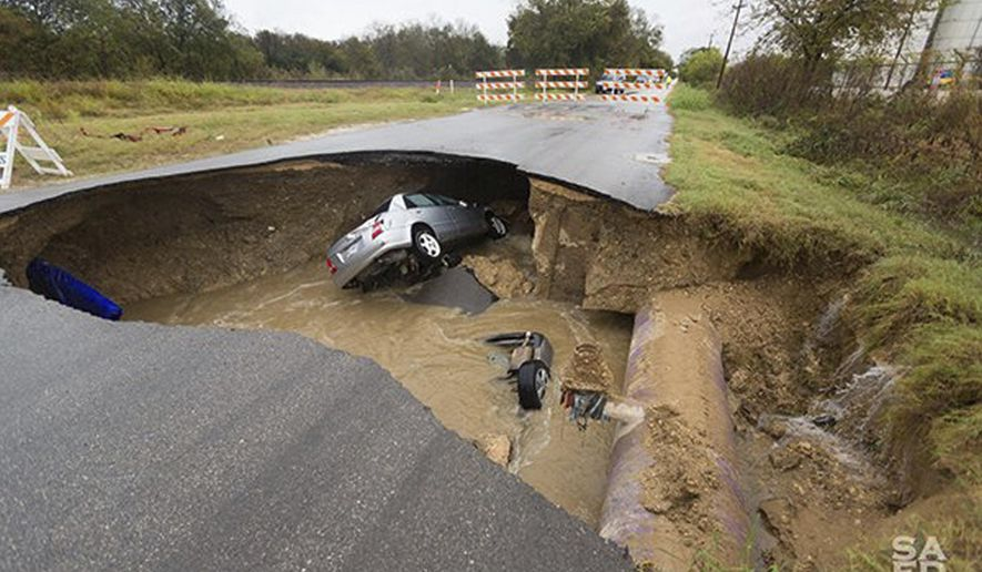 This Dec. 5, 2016, photo provided by the San Antonio Fire Department shows a sinkhole that opened up Sunday in San Antonio. Officials say Bexar County Sheriff's Deputy Dora Linda Nishihara an off-duty sheriff's deputy died and others were injured when two vehicles plunged into a water-filled sinkhole. Utility officials say the sinkhole appeared after a sewer line ruptured during heavy rain. (San Antonio Fire Department via AP)
